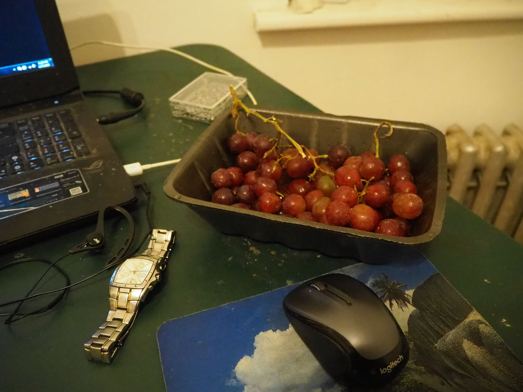 the grapes sitting on a green table in an apartment with a laptop and mouse